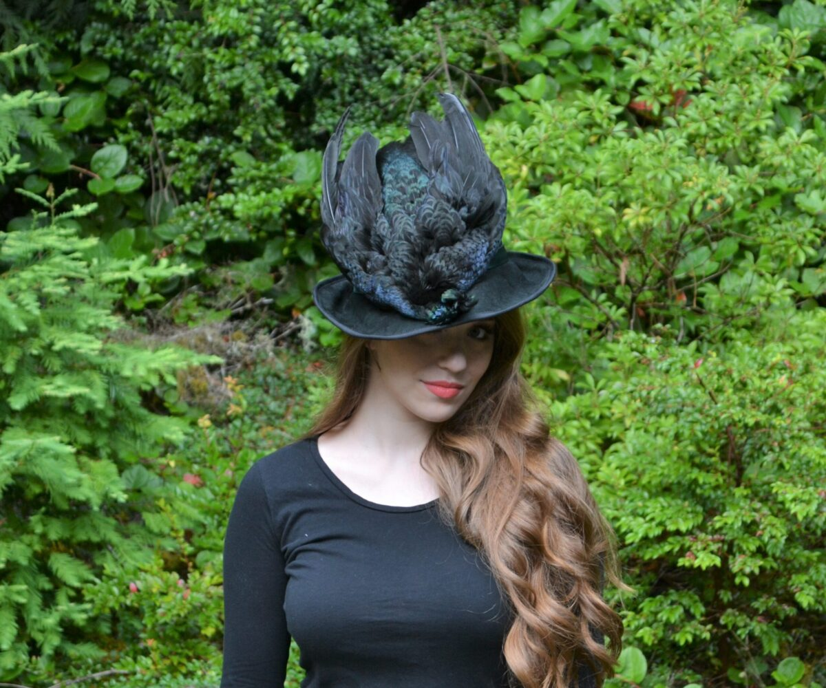 A black hat with a shimmering taxidermy bird on top, modelled by a young woman.