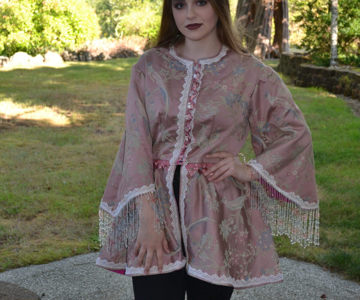 A muted pink top with floral patterns and wide sleeves, beeded trim hanging from the cuffs, worn by a young woman.