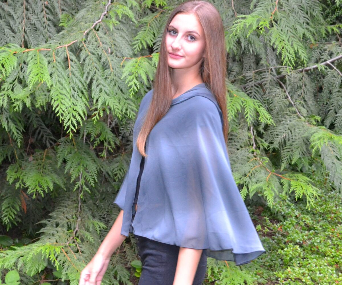 A cloudy grey shoulder-length capelet, hood down, modelled by a young woman.