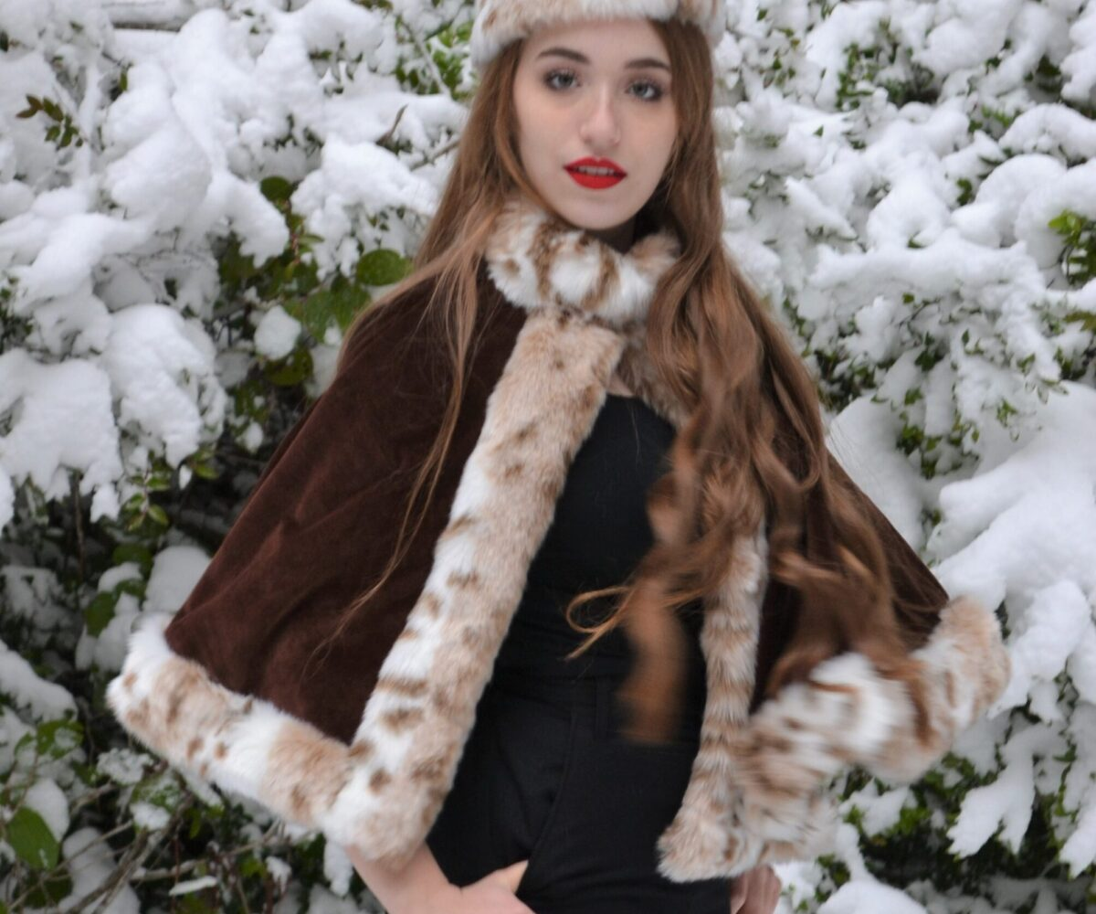 A fur-trimmed brown capelet and matching fur pillbox hat, modelled by a young woman.