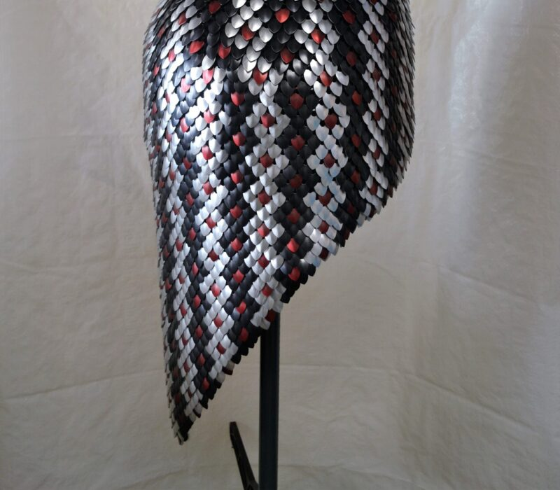 Side view of a reptile-pattern scalemaille skirt, showing the slope of the hemline.