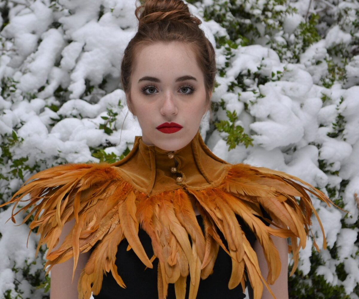 A golden brown collar with brown feathers fanning out around the edges, modelled by a young woman.