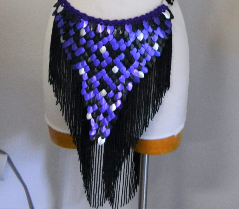 A blue and black set of matching scalemaille - a long loincloth with black trim, and a collar with blue trim.