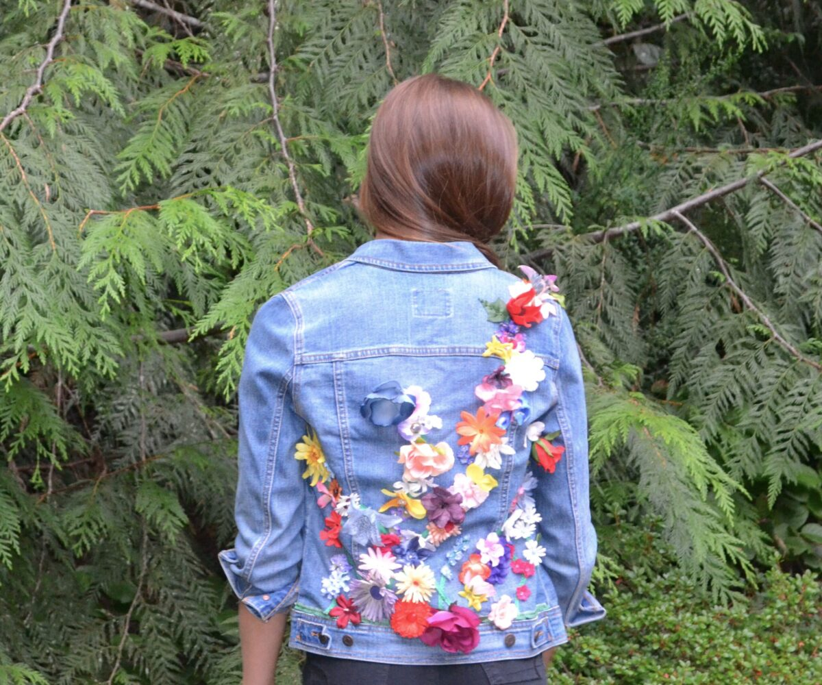 A denim jacket with colorful silk flowers climbing across the back, modelled by a young woman.