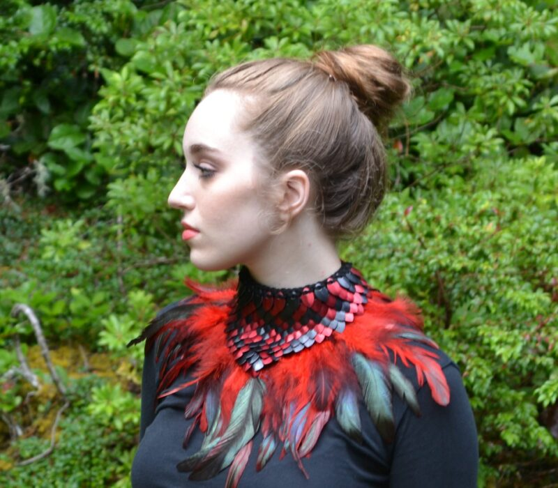 A black and red dragonhide collar with matching feather trim, worn by a young woman.