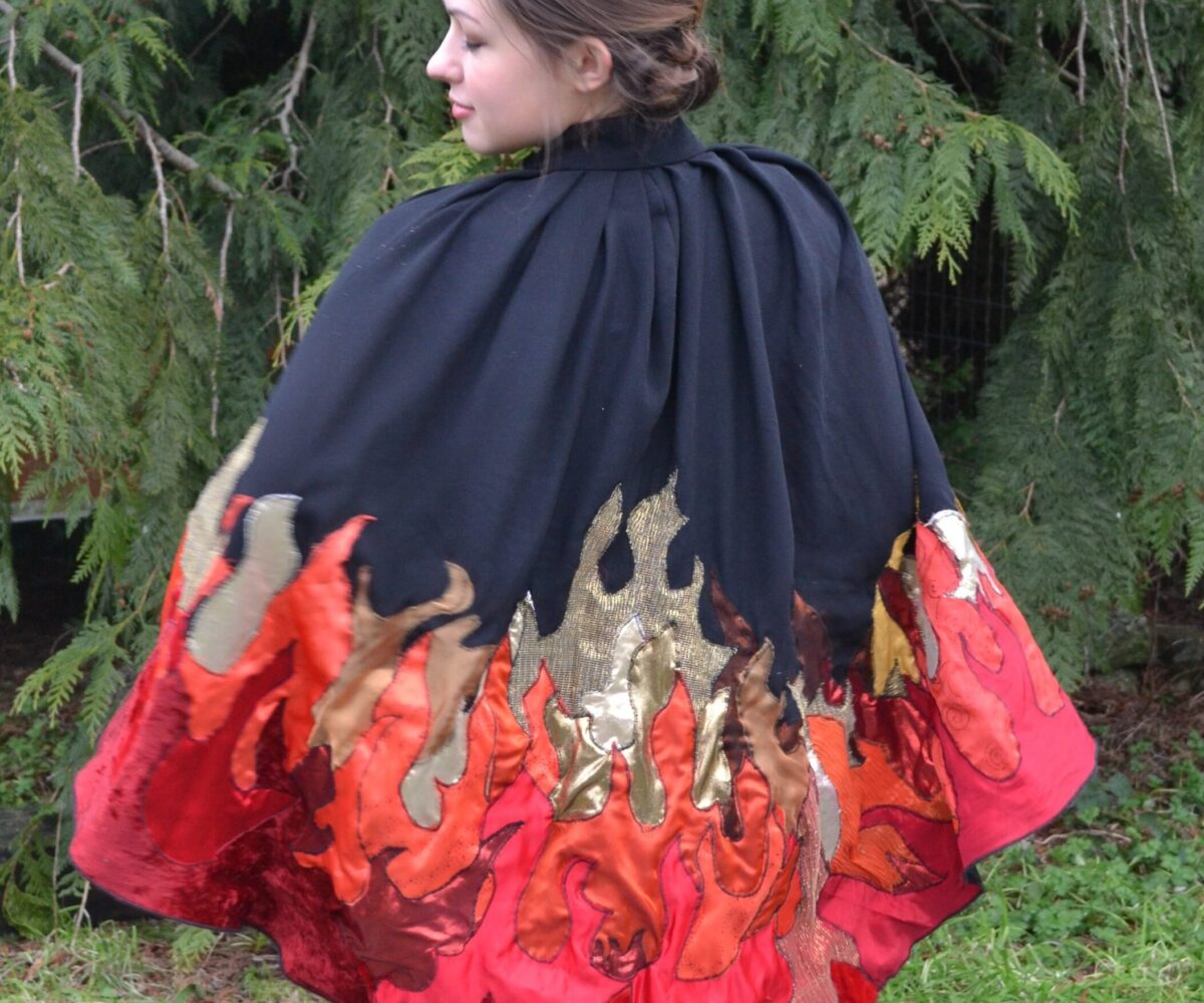 A black cape with red, orange, and gold flames apliqued climbing from the bottom edge, modelled by a young woman.