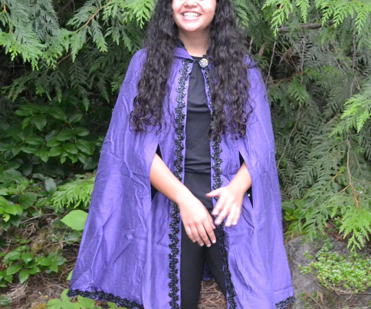 A purple cape with black trim aroubnd the edges, worn by a young woman.