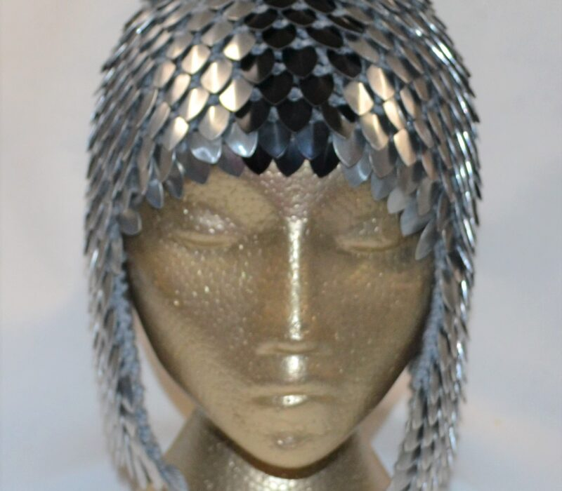 A silver dragonhide hat with ear flaps and a black and grey pompom.
