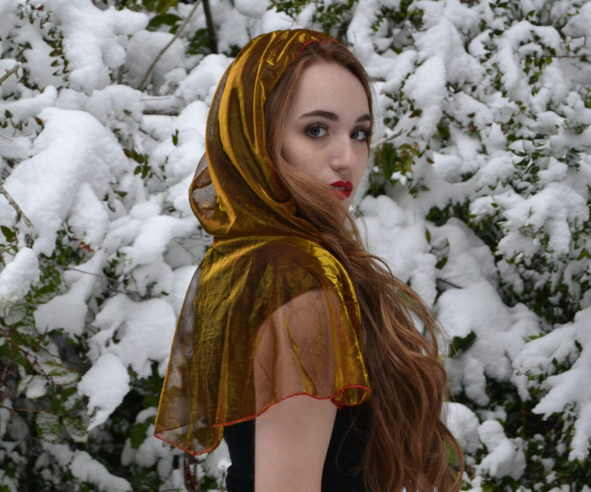 A sheer gold capelet, hood up, modelled by a young woman.