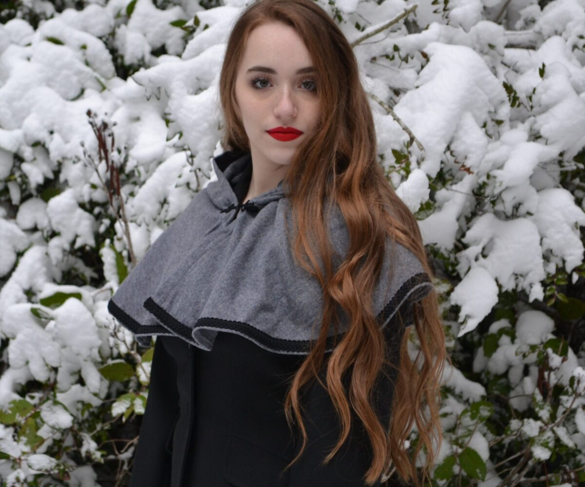 A grey capelet with black trim, the hood lowered, modelled by a young woman.