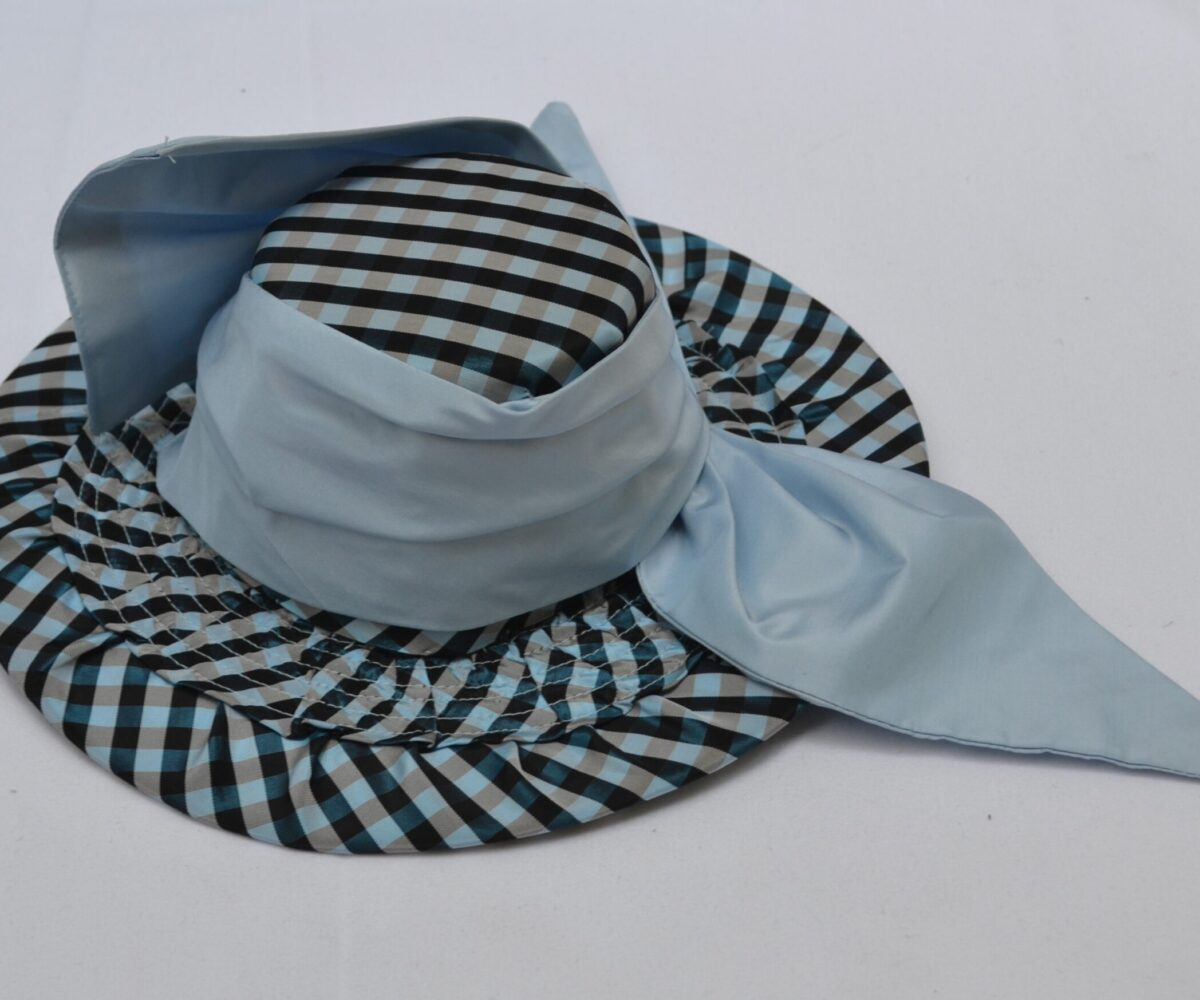 A black and tan gingham hat with a wide brim and neutral grey ribbon.
