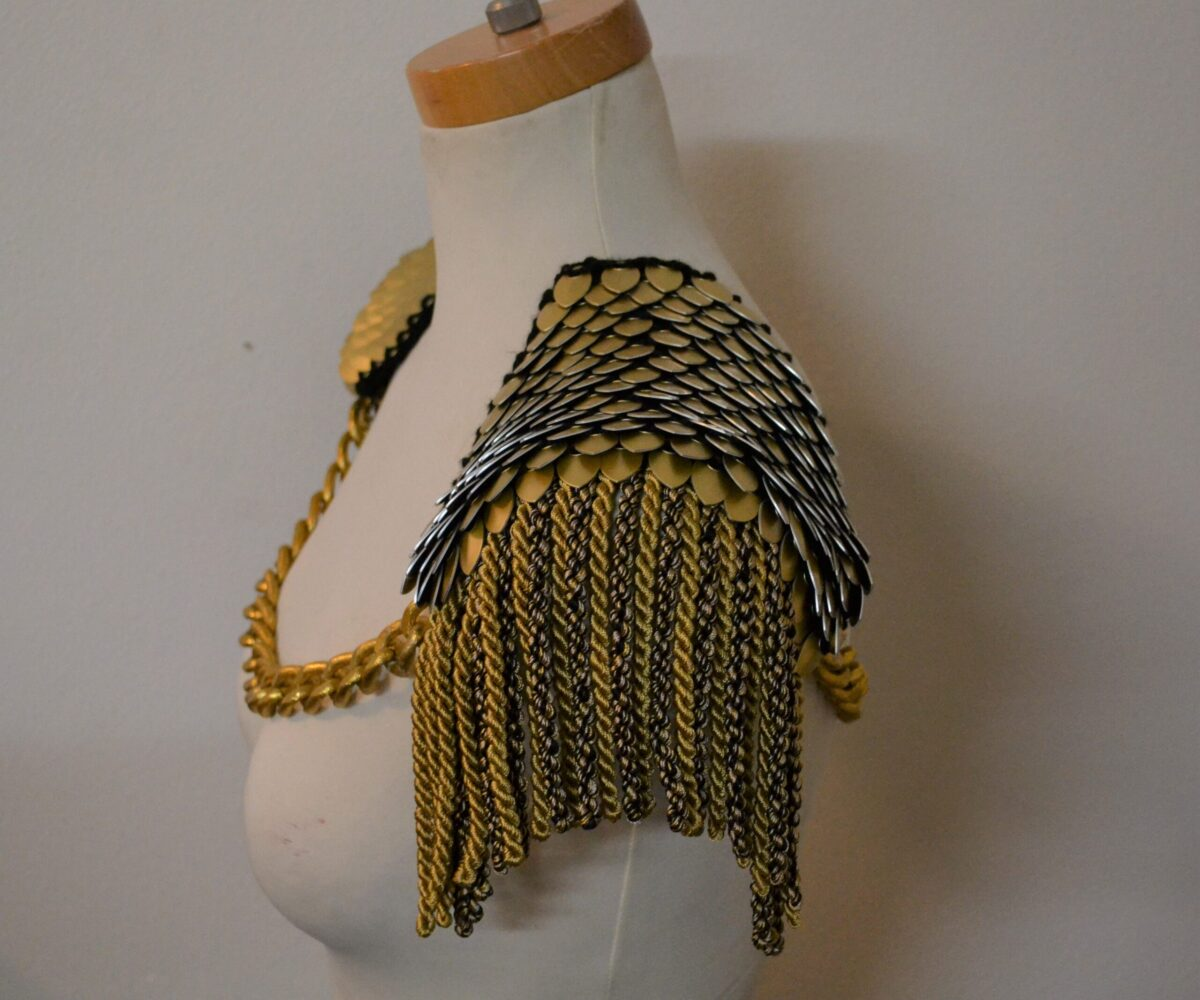 Gold knitted scalemaille pauldrons with gold rope trim hanging from the shoulders and thick gold chains connecting both shoulders.