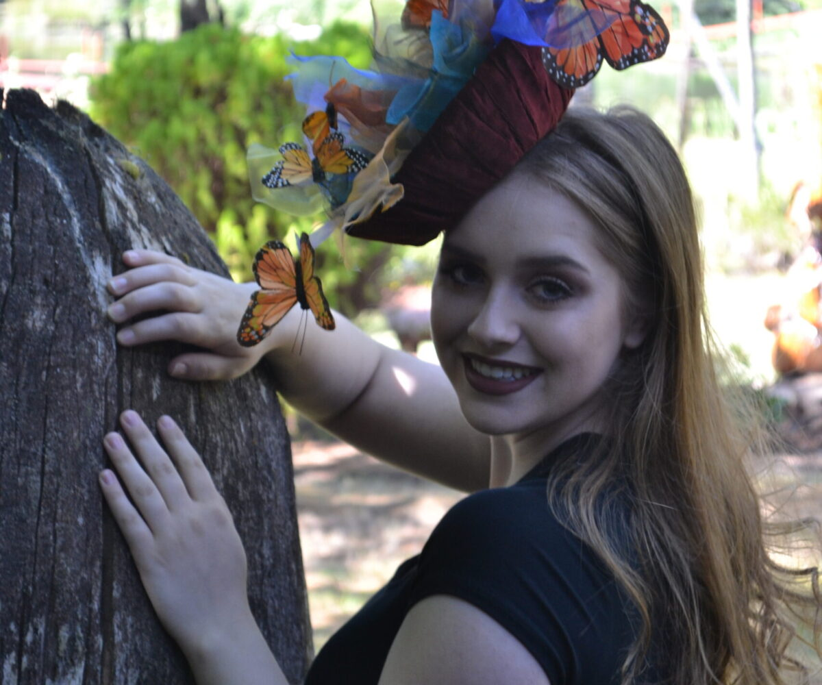 A hat shaped like a basket of sheer colors and monarch butterflies, worn by a young woman.