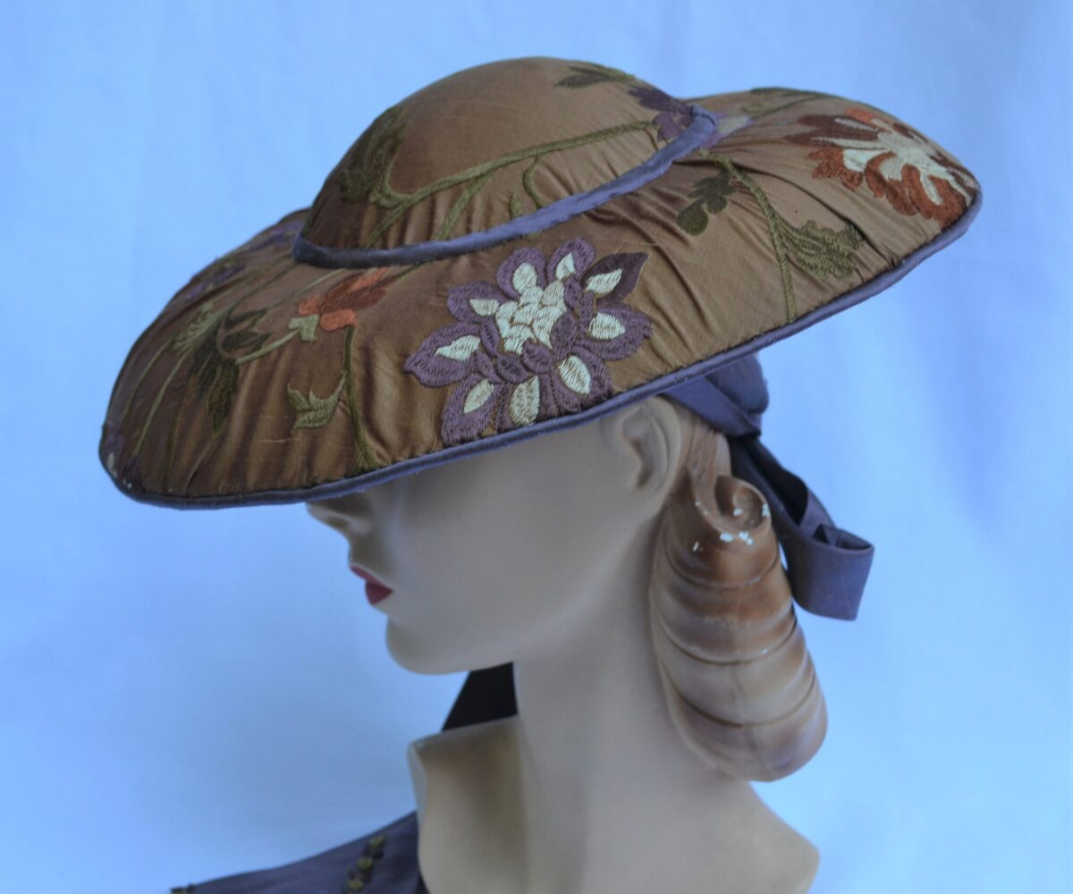 A wide-brim, shallow floral hat on brown fabric, with a blue ribbon.