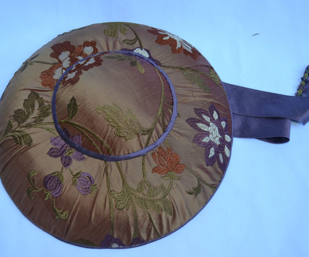 Top view of a floral wide-brim hat with gray-blue ribbon
