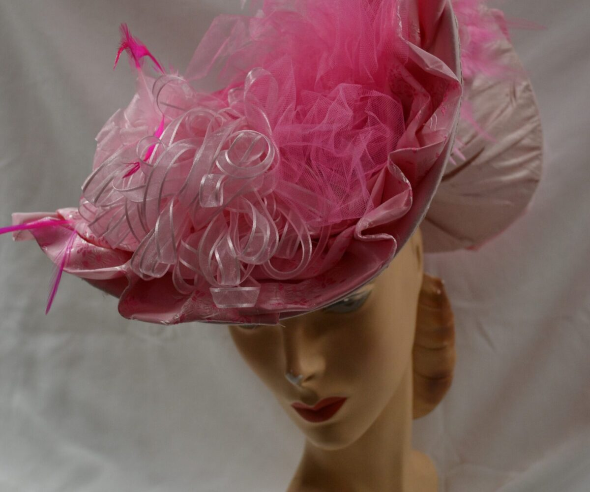 A pink and cream hat with a wide, curved brim, covered in pink ribbons, toulle, and feathers.