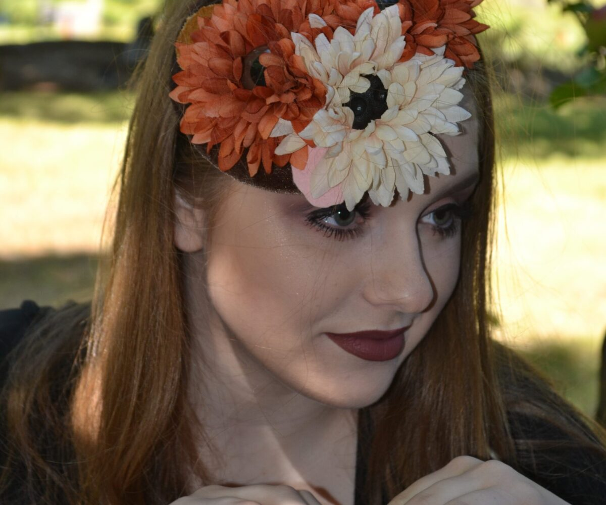 A young woman wearing a fascinator with large flowers, at the center of each flower is a glassy eye.