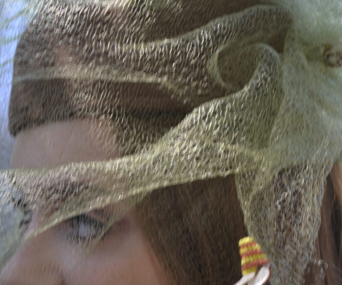 A yellow veil with small bees attached throughout, modelled by a young woman.