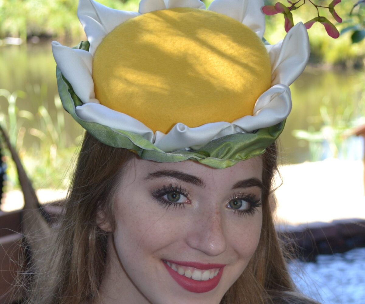 A young woman wearing a fascinator with a large yellow top, white fabric petals, and a green base.