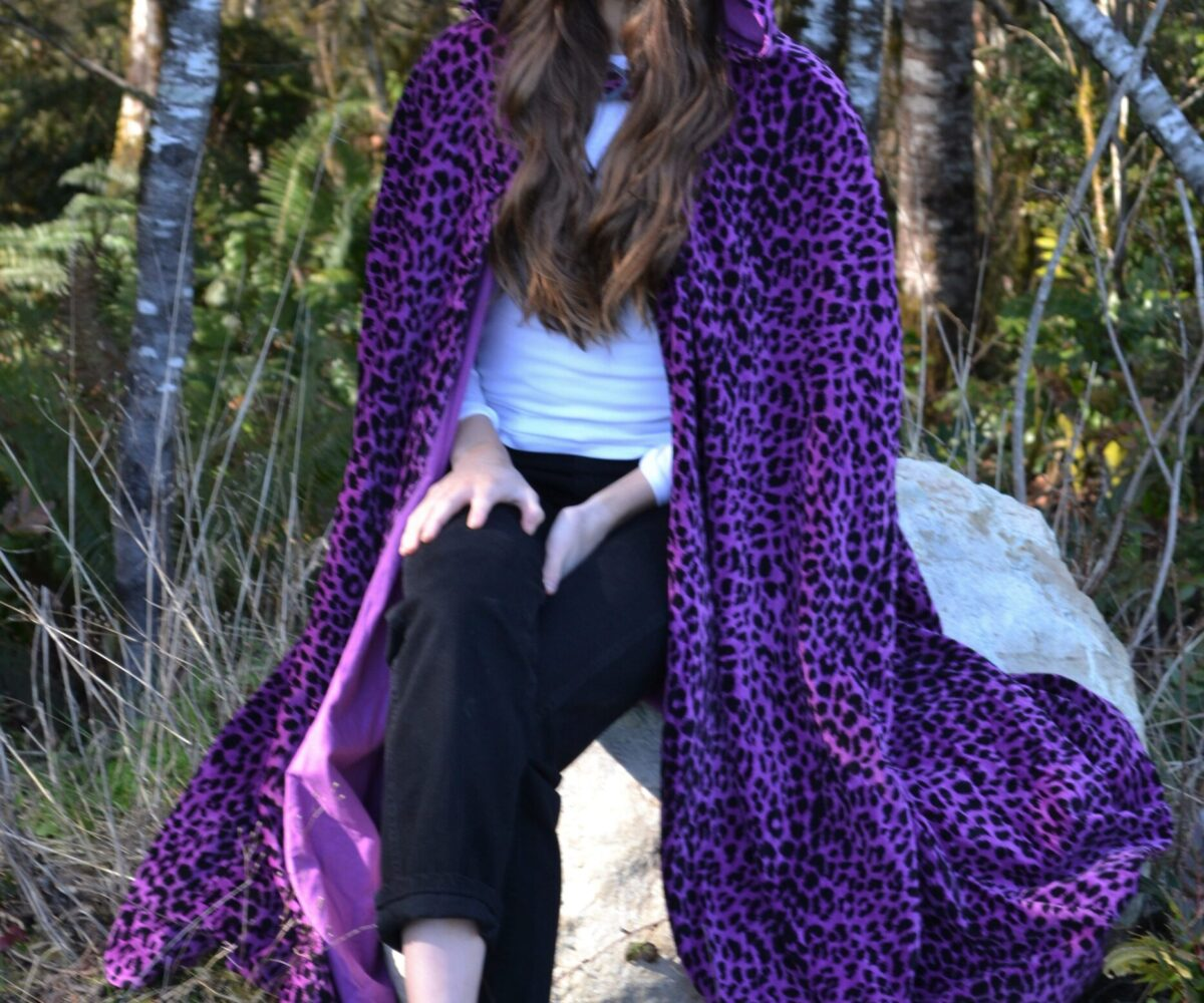 A long purple leopard-print cloak, hood up, modelled by a young woman.