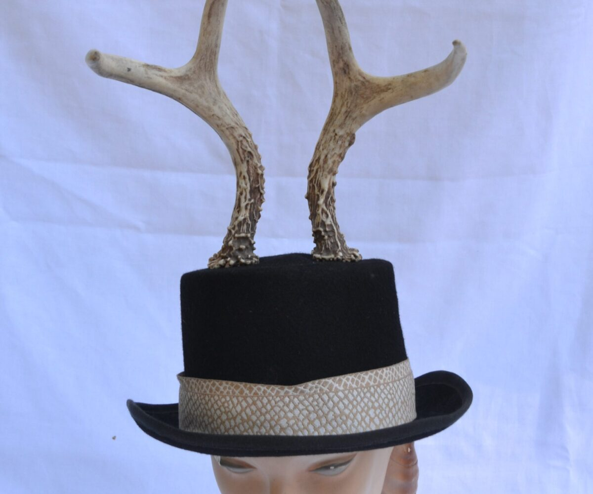 A black top hat with an upturned brim, snakeskin pattern ribbon, and antlers sticking up from the top.
