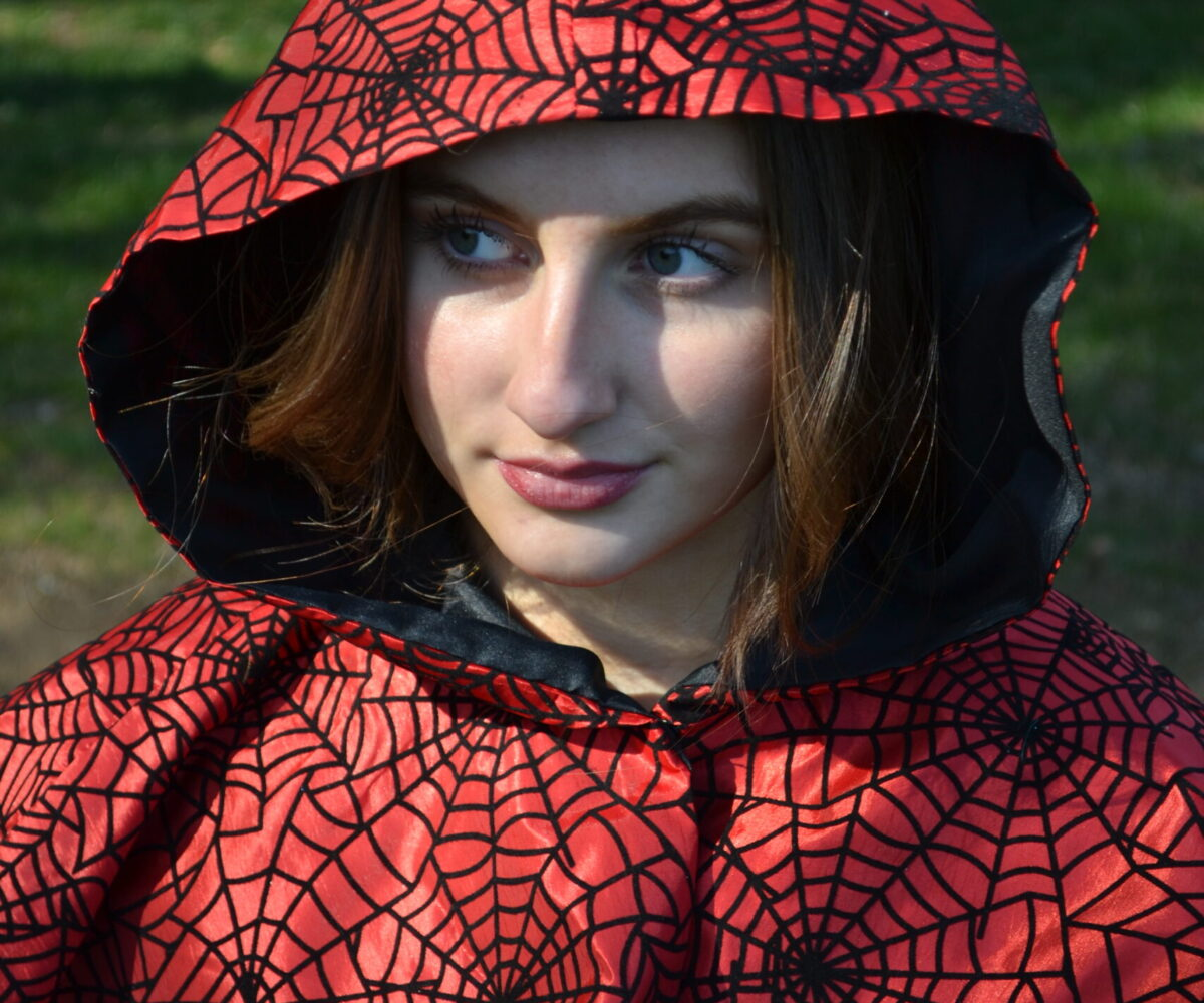A red capelet with black spiderweb patterns, modelled by a young woman.