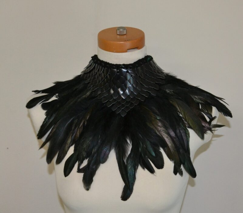 A black knitted dragonhide collar with black feather trim, shown on a mannequin