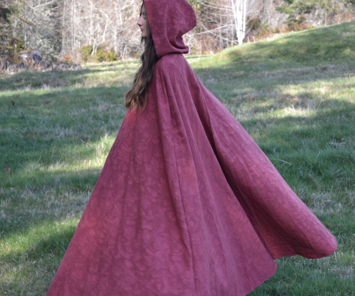 A long burgandy cloak, hood up, worn by a young woman.