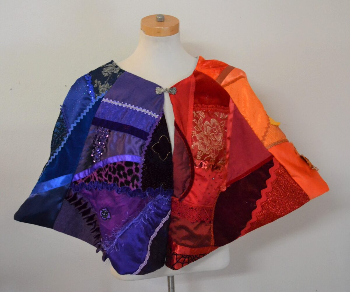 A split-color blue and orange patchwork capelet with a variety of patterned and textured fabrics and trims, shown on a mannequin.