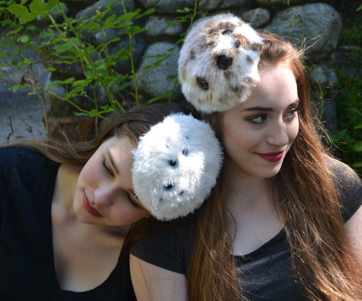 Two round, fluffy spider hats, one white, one white and brown.