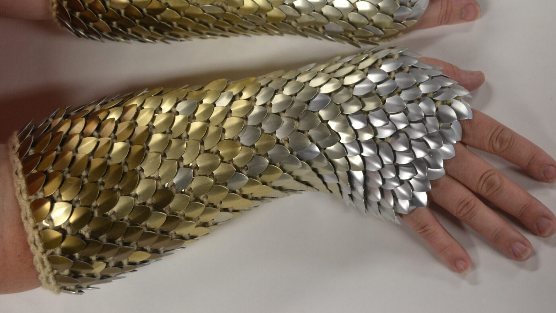 Long scalemaille gauntlets, cropped to show only one arm, with a bronze to silver gradient.